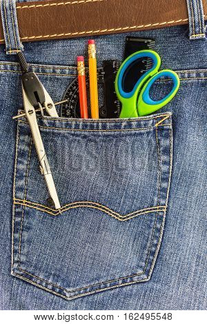 set of school tools in a back pocket of a blue denim jeans