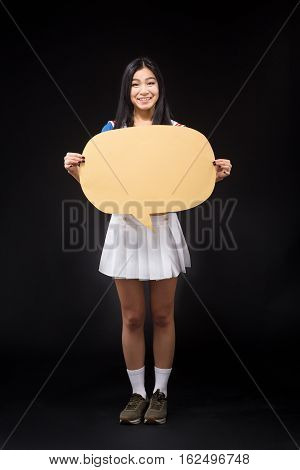 Happy Asian woman posing in full length and holding blank poster for expressing emotions or ideas isolated on black background in studio. Studio shot.