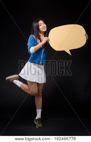 Happy Asian woman posing in full length and holding blank poster. Pretty woman holding note for expressing emotions or ideas isolated on black background in studio.