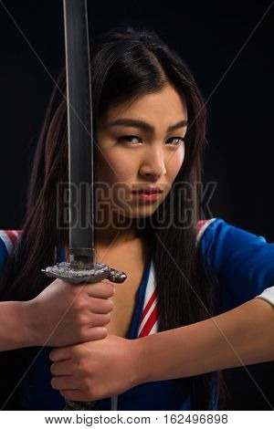 Closeup portrait of beautiful Asian lady with sword in studio. Lady holding sword in front of her.