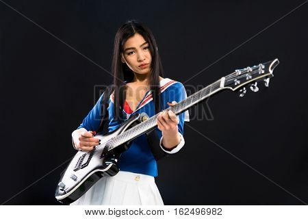 Asian rock star lady playing hard rock on guitar while posing for photographer isolated on black background in studio.