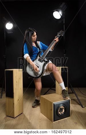 Asian rock star lady posing with guitar in studio. Brunette lady making hard rock music on guitar isolated on black background.
