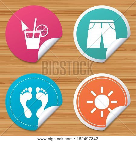 Round stickers or website banners. Beach holidays icons. Cocktail, human footprints and swimming trunks signs. Summer sun symbol. Circle badges with bended corner. Vector