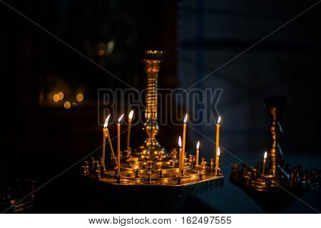 lighted candles standing on dark background inside the church the candles in the church religion candle holder