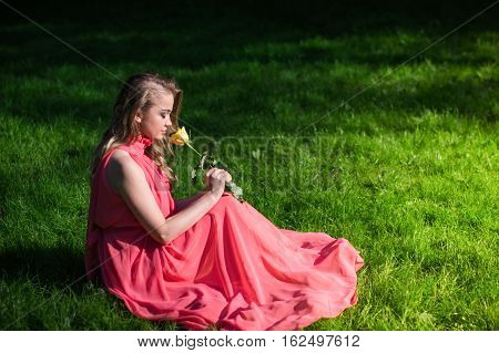 beautiful girl sniffing yellow rose in the Park