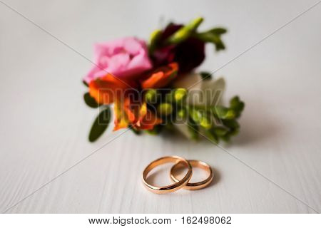 infinity sign of the rings wedding rings on a white backgroundwedding bands wedding jewelry wedding preparation pink boutonniere