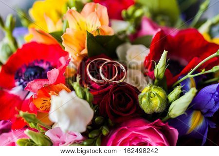 infinity sign of the rings wedding rings on a white backgroundwedding bands wedding rings lie on a bouquet of white blue yellow flowers and red roses bouquet of roses