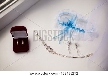 rings in red box garter of the bride women's earrings and chain lie on a white background wedding decorations are on the windowsill fees bride preparing for the wedding wedding jewelry