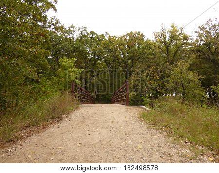 A walking bridge along a walking path over a small river in a public park in Minnesota.