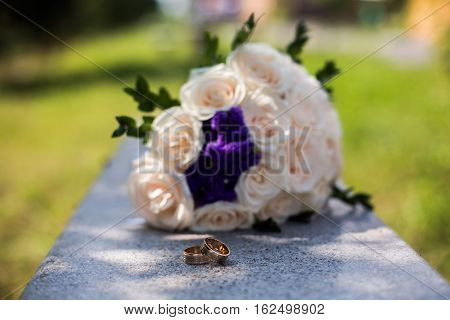 infinity sign of the rings wedding rings on a white backgroundwedding bands wedding rings lie near bouquet of white and pink peach roses a bouquet of roses wedding flowers