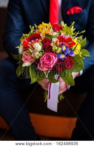 wedding flowers groom holds bouquet of white blue yellow flowers and red roses bouquet of roses bridal bouquet groom's fees