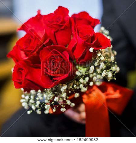 wedding flowers groom holds bouquet red roses bouquet of roses bridal bouquet groom's fees