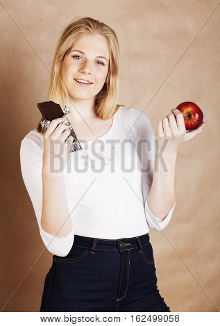 young beauty blond teenage girl eating chocolate smiling, choice between sweet and red apple