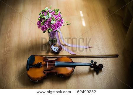 Wedding rings in the red box a violin and bow wedding flowers wedding bouquet of beautiful pink roses and white flowers rose bouquet wedding preparation wedding jewelry