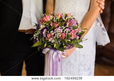 wedding flowers wedding bouquet the bride and groom sitting next to the bride girl holding a bridal bouquet of pink blue and white flowers wedding ceremony gown