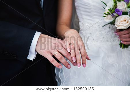 Bride and groom next to wedding rings on their hands male and female hand with wedding rings wedding ceremony together forever wedding flowers wedding bouquet white roses
