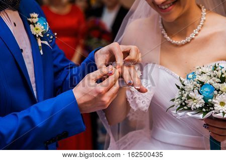Bride and groom next to the groom dress for the bride male and female hand with wedding rings wedding ceremony together forever wedding flowers wedding bouquet hands on bouquet moment happiness