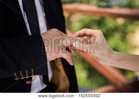 Bride and groom next to the groom dress for the bride male and female hand with wedding rings wedding ceremony together forever time happiness