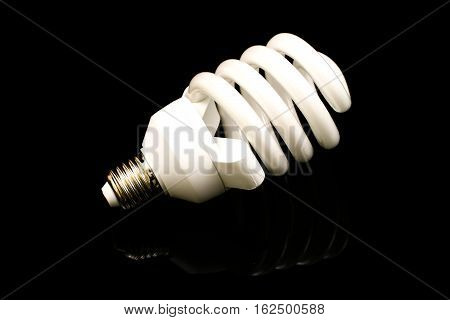 A white compact fluorescent bulb on a black background