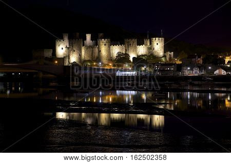 A long exposure of Conwy key at night with an iluminated Conwy castle you can see the reflections in the water of the river estuary