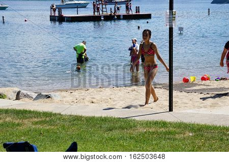 HARBOR SPRINGS, MICHIGAN / UNITED STATES - AUGUST 3, 2016: People enjoy swimming at the Zorn Park Public Beach near downtown Harbor Springs.