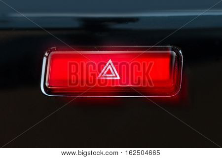 pushed red warning button with triangle pictogram and flasher light.