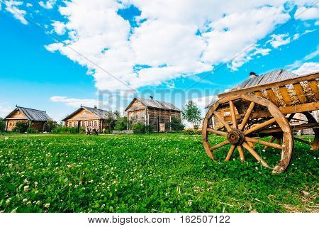 Green grass with clover in the foreground and a wooden hut on the background of the Slavic type. Blue sky with cumulus clouds. Summer day