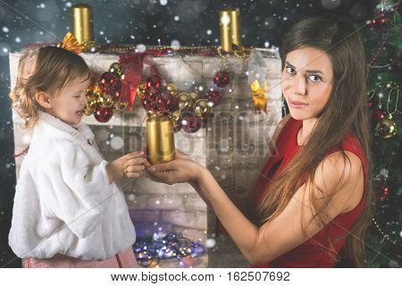 Cute baby and mum decorating a Christmas tree. Red balls. New Year 2017. Fairy tale. Mothercare is most important in children life. Baby and daughter