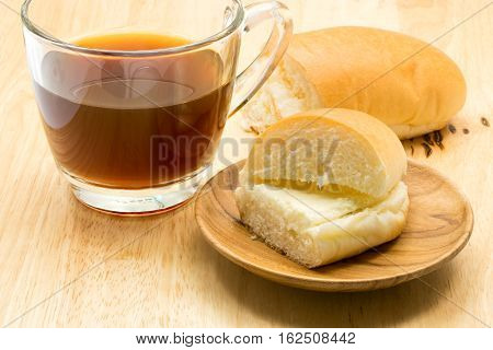 Hotdog bread filled with sweetened butter cream and a cup of coffee on wooden board