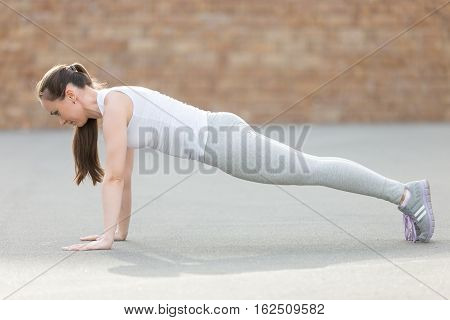 Sporty attractive young woman practicing yoga, standing in Plank exercise, Phalankasana pose, working out, wearing sportswear, outdoor full length, brick wall background