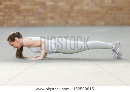 Sporty attractive young woman practicing yoga, standing in Four limbed staff exercise, chaturanga dandasana pose, working out, wearing sportswear, outdoor full length, brick wall background