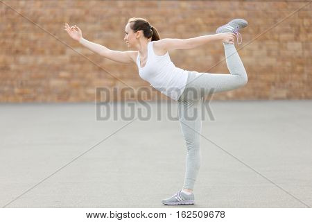 Sporty attractive young woman practicing yoga, standing in Lord of the Dance exercise, Natarajasana pose, working out, wearing sportswear, outdoor full length, brick wall background