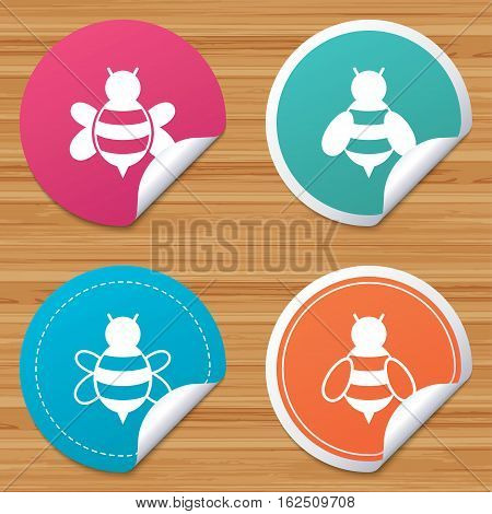 Round stickers or website banners. Honey bees icons. Bumblebees symbols. Flying insects with sting signs. Circle badges with bended corner. Vector