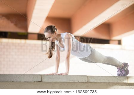 Sporty young girl practicing yoga, standing in Push ups or press ups exercise, phalankasana, Plank pose, working out, wearing sportswear, outdoor full length, urban background