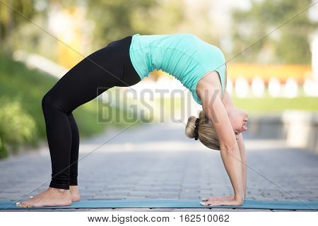 Sporty attractive young woman practicing yoga, staying in Bridge exercise, Urdhva Dhanurasana pose, working out, wearing sportswear, outdoor full length, street background