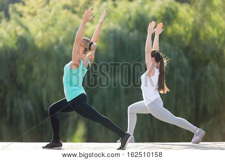 Group of two sporty attractive young women practicing yoga, standing in Warrior one exercise, Virabhadrasana 1 pose, working out, wearing sportswear, outdoor full length, street background