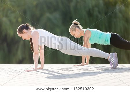 Group of two attractive sport young women practicing yoga, standing in Push ups or press ups exercise, phalankasana, Plank pose, working out, wearing sportswear, outdoor full length, street background