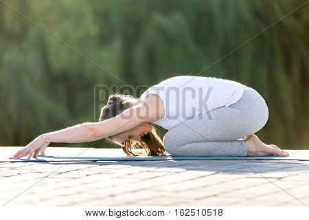 Sporty beautiful young woman practicing yoga, sitting in Child exercise, Balasana pose, working out, wearing sportswear, outdoor full length, street or park summer background