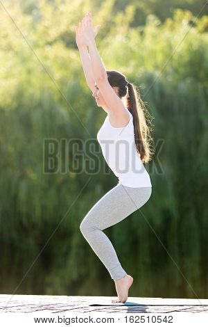 Sporty beautiful young woman practicing yoga, standing in Chair exercise, Utkatasana pose, working out, wearing sportswear, outdoor full length, street or park summer background