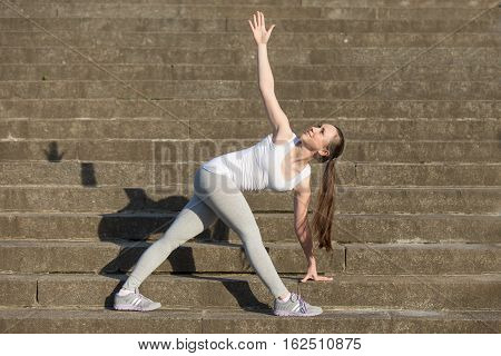 Sporty attractive happy young woman practicing yoga, standing in Revolved Triangle exercise, Parivrrta Trikonasana pose, working out, wearing sportswear, outdoor, stone stair background with a shadow
