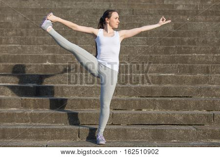 Sporty attractive young woman practicing yoga, standing in Extended Hand to Big Toe exercise, Utthita Hasta Padangustasana pose, working out, wearing sportswear, outdoor, stone stair background