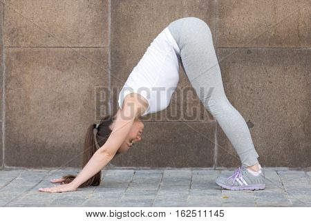 Sporty attractive young woman practicing yoga, standing in Downward facing dog exercise, adho mukha svanasana pose, working out, wearing sportswear, outdoor full length, city street, wall background