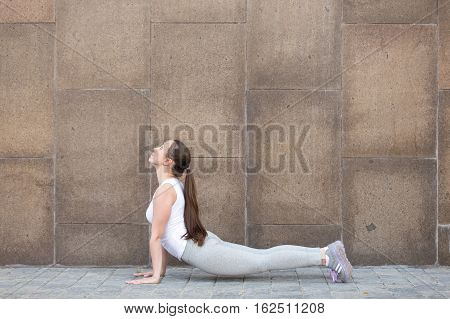 Sporty attractive young woman practicing yoga, doing Upward facing dog exercise, Urdhva mukha shvanasana pose, working out, wearing sportswear, outdoor full length, stone wall background. Copy space