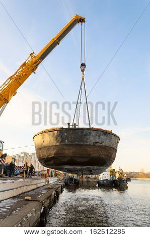 MOSCOW, RUSSIA - NOVEMBER 11, 2016: State Unitary Enterprise Mosvodostok performs recovery vessels on coastal winter parking. Car crane lifts the barge from river.