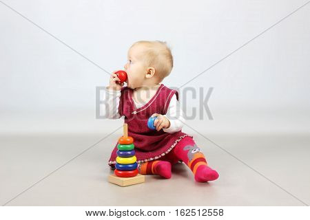 Studio shot of an adorable baby girl in red dress playing with wooden toys.