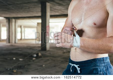 Front view of man with naked torso touching elastic bandage in hand.