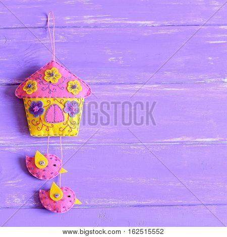 Decorative felt house with birds isolated on wooden background with copy space for text. Handmade felt wall decoration to create attractive and original interior design. Top view