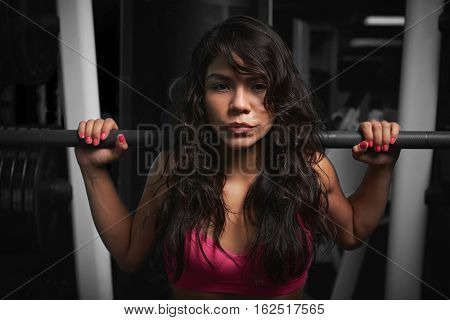 Woman holding barbell close up on dark modern  gym background