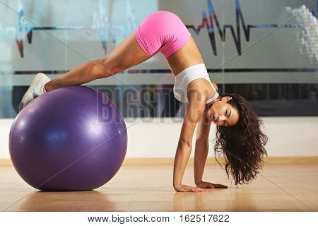 Woman doing fitness with aerobic ball in gym. Aerobic trainer woman