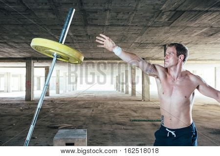 Side view of strong man throwing crossbar with weight. Horizontal indoor shot